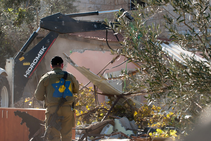 An Israeli soldier carries out a demolition order 負責執行清拆令的以色列士兵