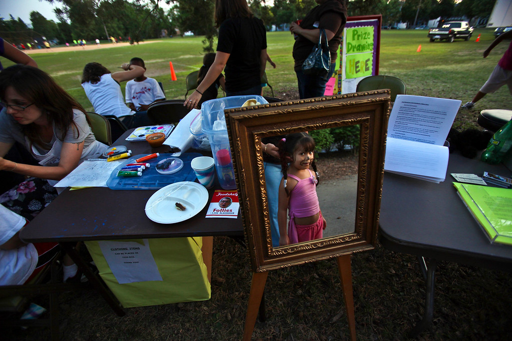 A little girl checked out her appearance in the mirror after getting her face painted at National Night Out in Minneapolis, Minn. © STAR TRIBUNE