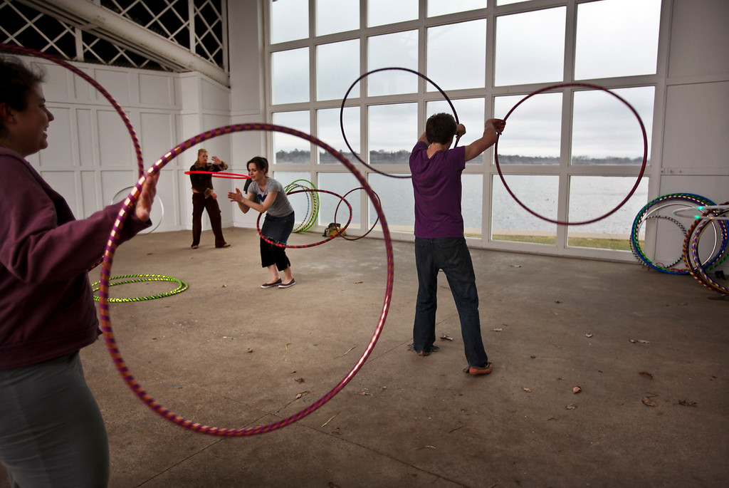 """A group of people hoola hooped with multiple hoops during a """"hoopla"""" at the Lake Harriet bandshell with the Hoop Twin Cities Club."""