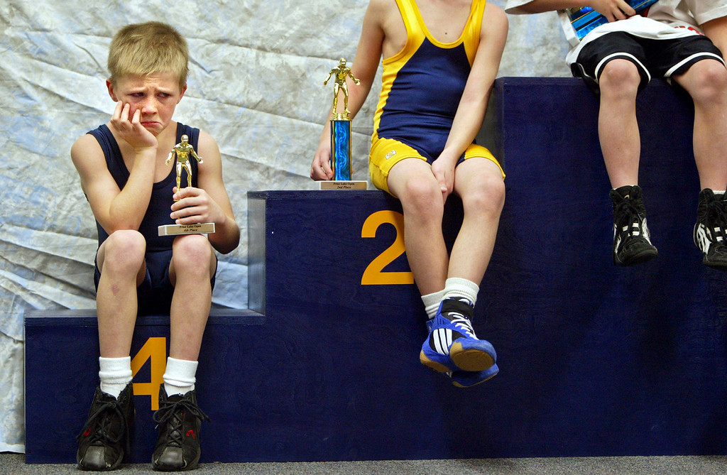 Jimmy Cates was not too happy about posing with his trophy after competing in a youth wrestling tournament at Prior Lake High School. © STAR TRIBUNE