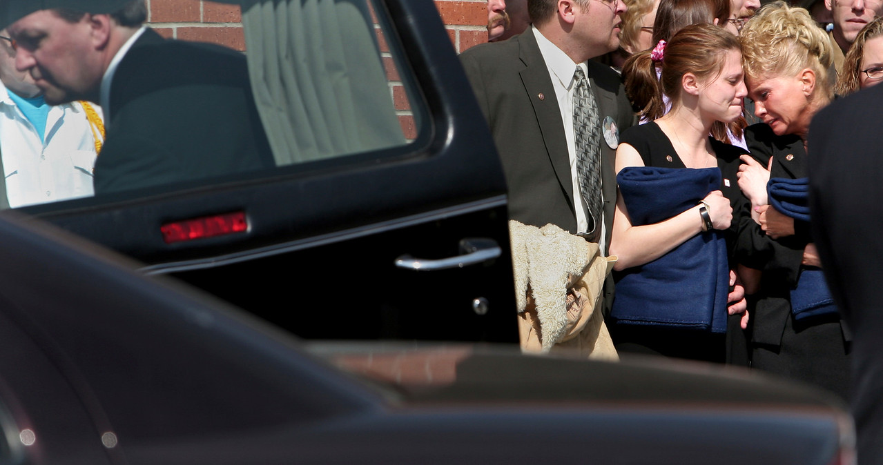 Tonya Bruce and Vickie Bruce cried together as the casket of their brother and son Cpl. Travis Bruce is carried into the hearse after the funeral in Rochester, Minn. © STAR TRIBUNE