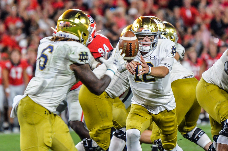 Notre Dame quarterback Ian Book (12) flips the ball back to runningback Tony Jones (6) during the game between Georgia and Notre Dame, Saturday, September 21, 2019 at Sanford Stadium in Athens, Georgia. (Photo: Nicole Seitz)