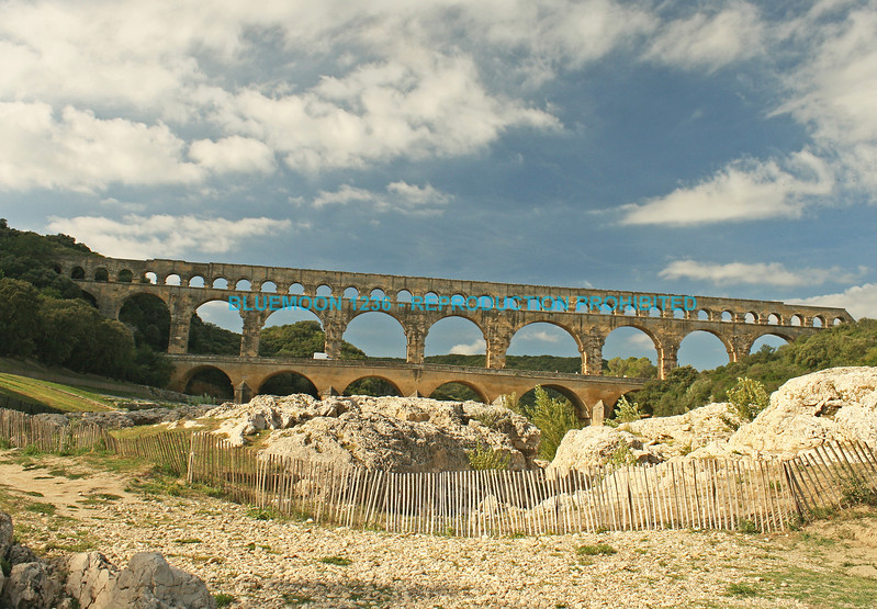 """Pont Du Gard aqueduct and bridge crossing a river with boulders and stabilization fencing in the foreground.  The aqueduct is framed by a bright blue sky with puffy and wispy white clouds.<br /> <br />  <a href=""""http://www.bluemoon1236.smugmug.com"""">http://www.bluemoon1236.smugmug.com</a>; bluemoon1236 ,Bluemoon Fine Photography ,Bluemoon Fine Photography"""