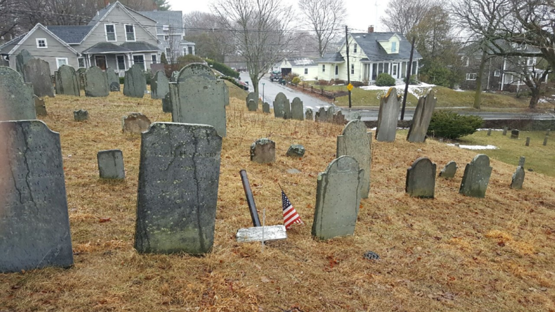 Haskell's stone is to the left of the American flag. For help in locating this grave, note that the street running left and right in the background is Pond St. The street running away from the viewer is Hillside Av. If you enter the cemetery through the narrow gate on Greenleaf St, bear left up to the high ridge that parallels Pond St. Follow that ridge to it's end and you will find the grave (in the southeast corner of the cemetery.)