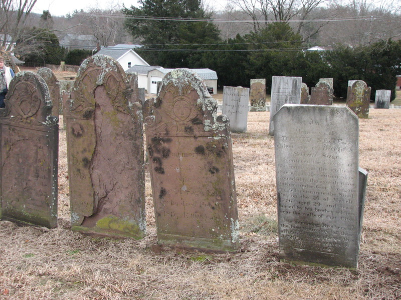 The cenotaph of David Sage is the white stone to the right in this photo. The graves of his parents are the brownstones to the left.<br /> Use this photo to help locate the stone, which is situated in the northeast corner of the cemetery, about nine rows in from Portland Street, and halfway between the north boundary of the cemetery and the prominent Gildersleeve tomb. The buildings in the background can also be used to help you find the right spot.
