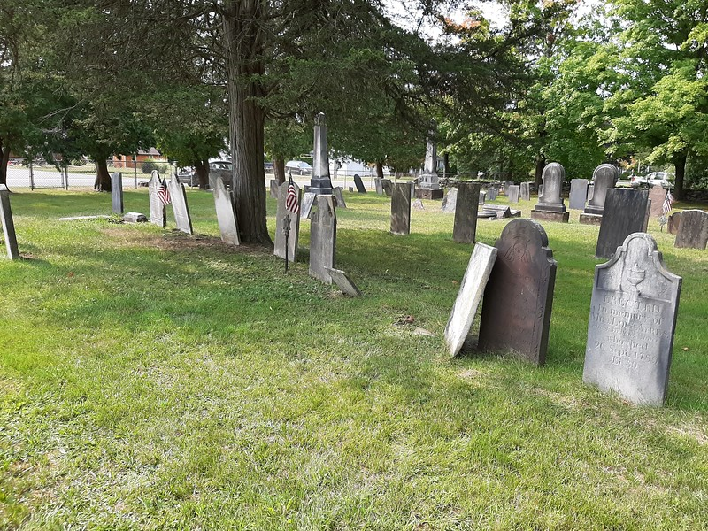 Eleazar Ayres' gravestone is the white one leaning against his wife's brown stone. Use this photo to help locate the grave. Batchelor Street is seen in the distance. Walk through the pedestrian gate and straight into the the cemetery until you come to the ninth stone in the row.