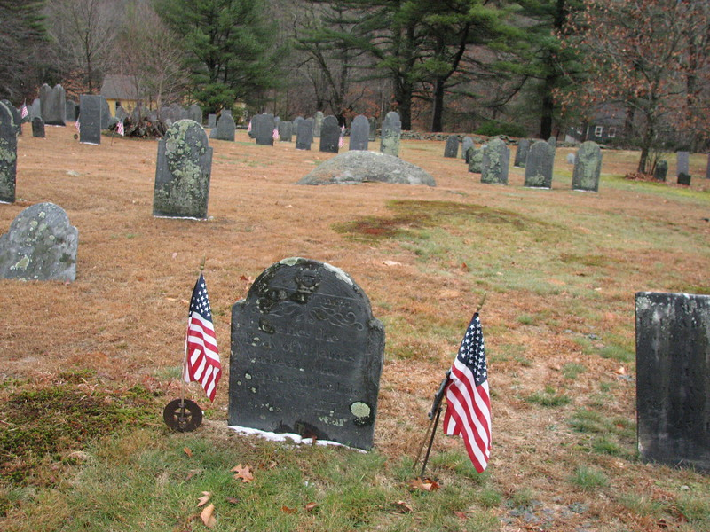 Gravestone of James McKeen, between the flags. To locate this grave, note the large rounded bedrock feature in the background. The photo is taken facing toward the street, and that rock will be found towards the center-rear of the cemetery. Use it to guide you to the grave.