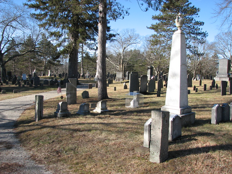 If you enter the cemetery via the gate nearest Causeway St, you quickly come to a road on your left. If you stop and look down this road, this is your view. Tisdale's gravestone is in the left-center with the flag and a piece missing from its top. The inscription is on the far side of the stone.