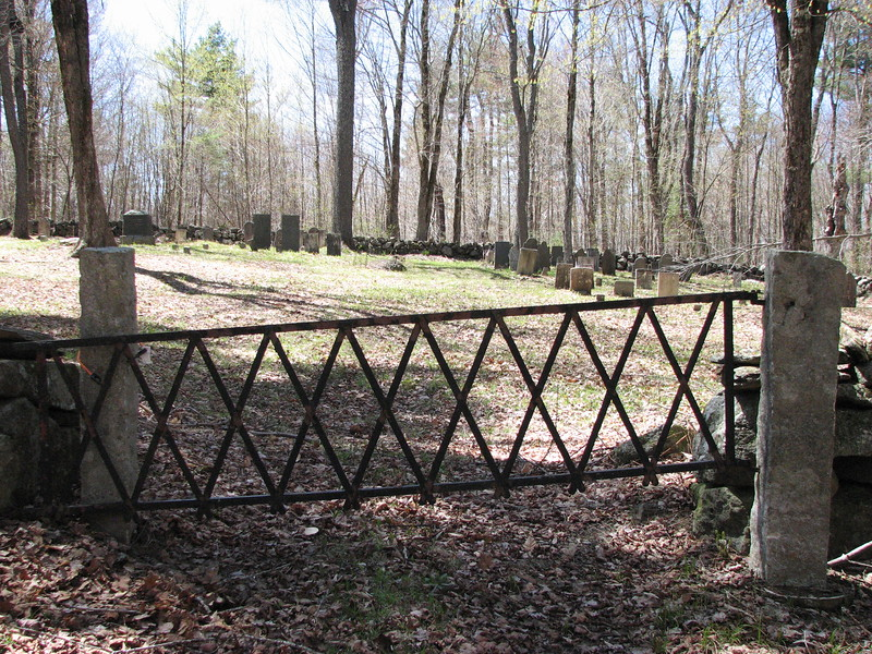 Gate of the cemetery, reached by walking 0.6 miles down an old dirt road. To locate the Barker grave, note the two tall dark square-top stones together in the left-center background. The Barker grave is the round-top one just visible to the left of the left-hand dark stone