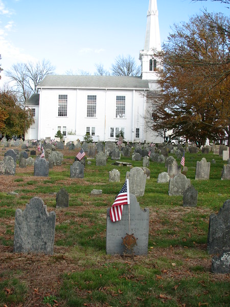 Use this photo to locate the grave. The cemetery is a narrow triangle of land west of the church. Nathaniel Church's stone (in the foreground with the flag) is 16 rows from the church (be careful not to count footstones) and 11 stones from the south side of the cemetery. If you enter from the gate opposite the house at 8 Commons, it will be one row to your right, then in 11 stones.