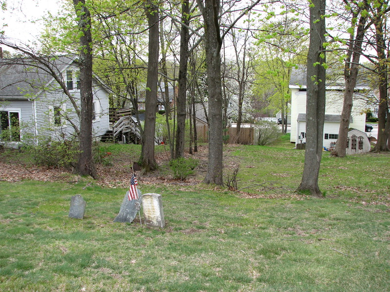 The grave of Samuel Blaisdell is in the Revolutionary War section of the cemetery, which is the northeast corner. Use this photo to help locate the grave. Look for these houses beyond the east edge of the cemetery. Main Street can be seen in the background. Blaisdell's stone is marked with a flag in this photo.