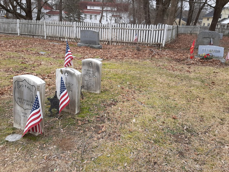 To locate the gravestone, use the cemetery entrance that's directly behind the old church (of the three entrances, it is the one furthest left.) Drive in noting the white picket fence running parallel with the roadway. At the point where the fence jogs out to widen the cemetery, stop the car and find these three stones along the road on your left. The angle of the fence can be seen in this photo. Singleton's stone is the third one.