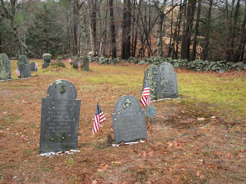 Samuel Treadwell's grave is flanked by flags. Use this photo to guide you to the grave. It will be found about halfway back in the cemetery, and about 40 feet from the south side wall, in an area sparsely occupied by gravestones.