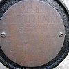 Close up of the inscription on the brass disk on the cross placed in front of the grave.