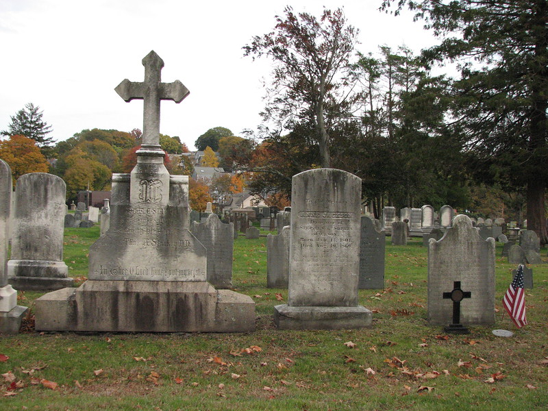 Use this photo to locate Thayer's gravestone. The cross-topped monument (unique in this area of the cemetery) is two stones to the left of Thayer's, looking east. Thayer's grave is decorated with the US flag.