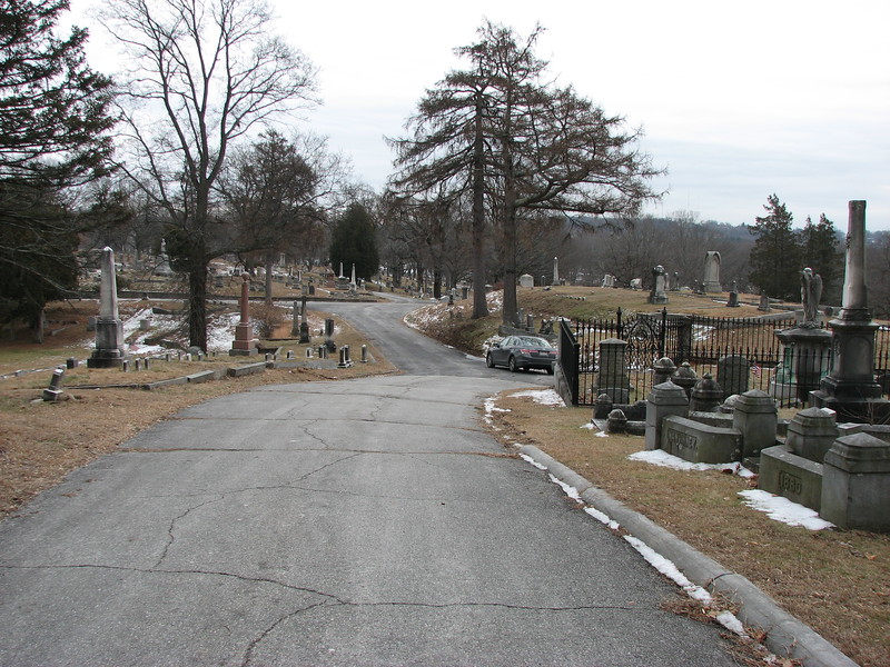 To locate the grave: Enter the cemetery via the main gate, then take your first left (Elm Av) and follow that road north as it parallels Webster Street. After passing the closed Chapel Gate, take your next right onto Chapel Avenue. Just over the crest of the hill, this will be your view. The Gates obelisk is on the left, opposite a large wrought iron enclosure on the right.<br /> The grave is in Section 3 of the cemetery.