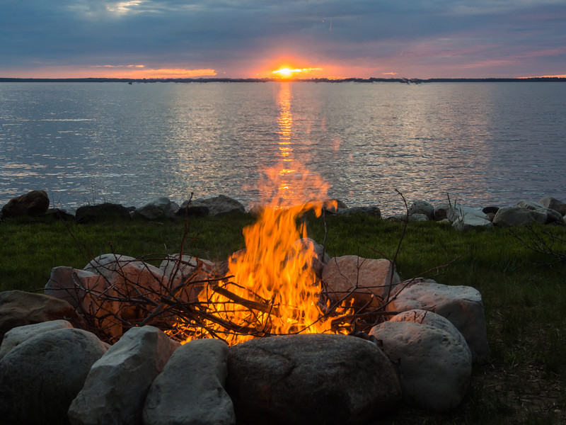 Sunset fire by the lake, burning off branches from cut down tree.