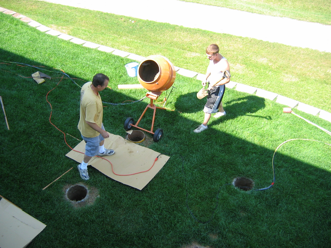 Jay & Jay mixing concrete for first deck post hole.
