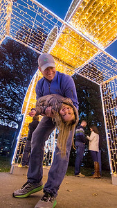 John Paul West of Irving, Texas holds his daughter Julie under one of the new light displays in downtown Effingham Saturday evening. Keith Stewart Photo