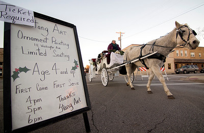 A horse-drawn carriage heads south on N. 4th Street passing a sign advertising ornament decorating for kids at Stang ART as part of the Hometown Christmas in downtown Effingham Saturday. Keith Stewart Photo