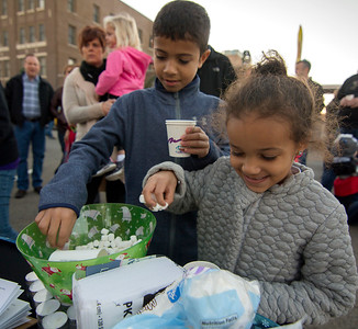 Five-year-old Amaya Griffiths, right, and her 9-year-old brother Keenan grab marshmallows for their hot chocolate Saturday at the Hometown Christmas in downtown Effingham. Keith Stewart Photo