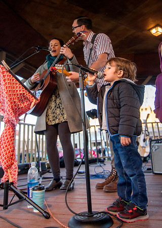 Erin Goldstein, left, and Jeff Corman, center, known as The Greyhounds, sing with help from Erin's four-year-old nephew Rhys during Saturday's Hometown Christmas in downtown Effingham.<br /> Keith Stewart Photo