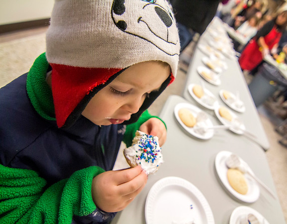 Three-year-old Kamden Koenig enjoys his cookie creation during the IGA cookie decorating Saturday in downtown Effingham.<br /> Keith Stewart Photo