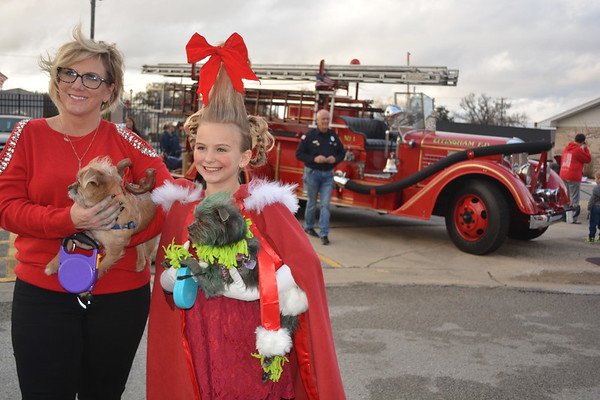 Ali Bloemer and Brileigh Bloemer, 10, of Teutopolis, hold their dogs, Sheffield and Addison. Brileigh came dressed as Cindy Lou Who. Sheffield came wearing antlers, to portray Max from The Grinch story. Addison, donned green hair and came is The Grinch. Dawn Schabbing photo