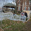 Anthony and Rebekah Robertson, and their daughter, Norah, 1, of Altamont have a family photo taken at the newest lawn ornament on the Effingham County courthouse square. Dawn Schabbing photo