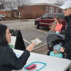 Susan Becker hands a ticket to see Santa to Morgan Flach. In the stroller is Summer Knight, 2. Dawn Schabbing photo