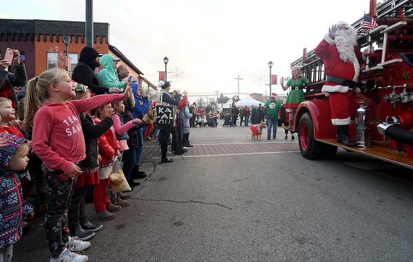 Santa waves to the crowd as he arrives in downtown Effingham during Hometown Christmas Saturday evening sponsored by the Downtown Effingham Business Group.  Chet Piotrowski Jr. photo/Piotrowski Studios