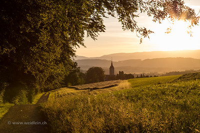 The Church and the rolling Swiss hills in hot sunshine