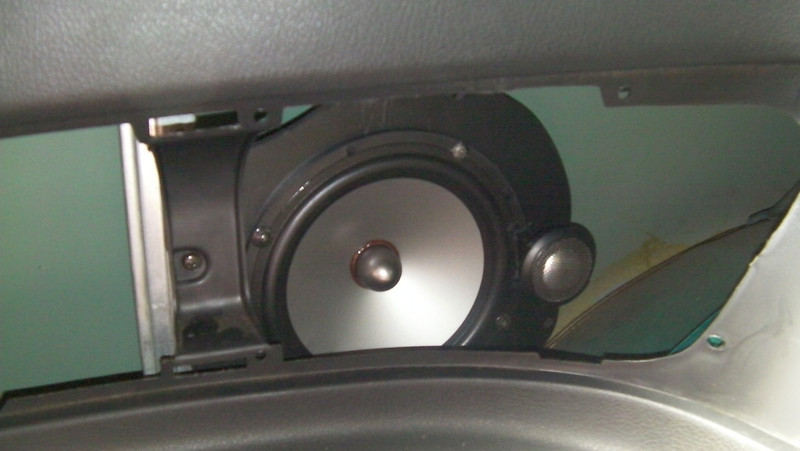 Speaker and adapter assembly mounted in vehicle.