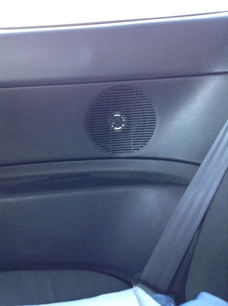 Rear panel speaker installation with grill