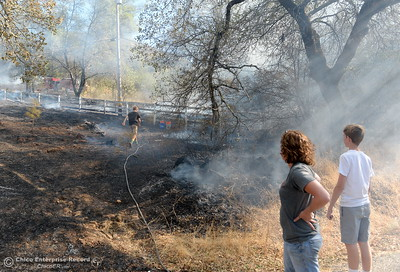 Amy Rohrer and her sons Ben, left and Max use a garden hose to help on a fire that started near 2485 Honey Run Road and ran up Butte Creek Canyon toward lower Paradise, Calif. Monday Oct. 9, 2017. (Bill Husa -- Enterprise-Record)