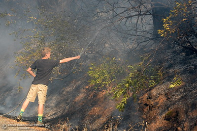 Ben Rohrer, 13, helps out with a garden hose on a fire that started near 2485 Honey Run Road and ran up Butte Creek Canyon toward lower Paradise, Calif. Monday Oct. 9, 2017. (Bill Husa -- Enterprise-Record)