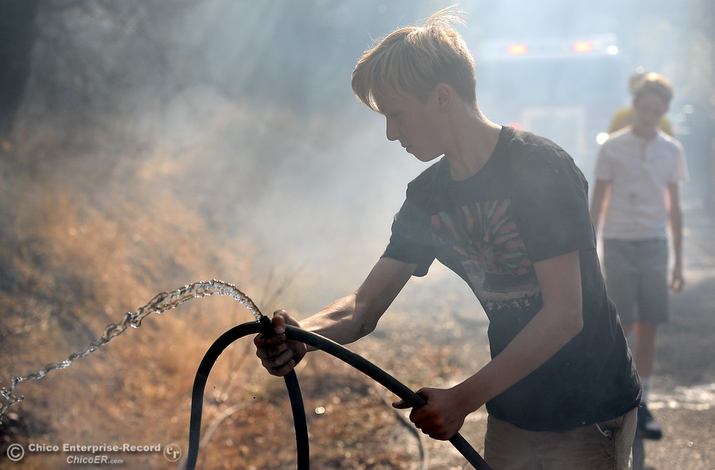 . Ben Rohrer, 13, helps out with a garden hose on a fire that started near 2485 Honey Run Road and ran up Butte Creek Canyon toward lower Paradise, Calif. Monday Oct. 9, 2017. (Bill Husa -- Enterprise-Record)