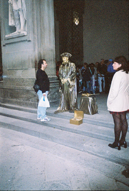 A sliver painted actor outside the famous museum Uffizi.  Home of Michaelangelo's David.
