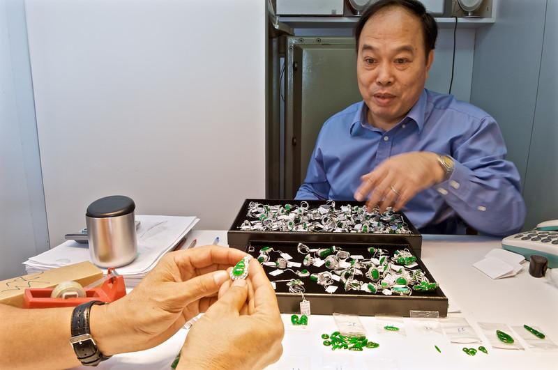 Un grossiste en jade présentant des pierres à un client dans son bureau du quartier de Yau Ma Tei. Hong Kong/Chine