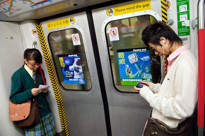 Deux adolescents se faisant face tout en s'ignorant à l'entrée d'un wagon de métro. Hong Kong/Chine