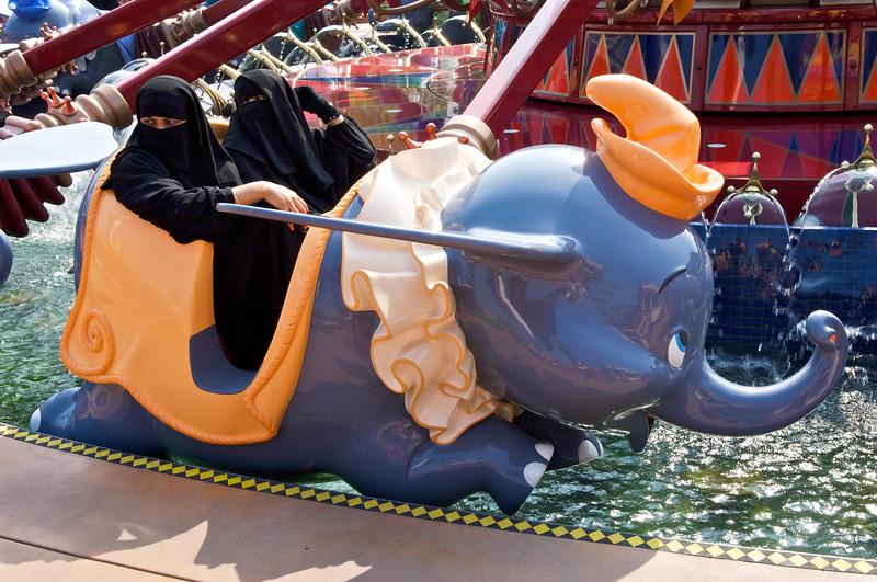 Deux femmes entièrement voilées dans un wagonnet à l'effigie de Dumbo l'éléphant sur un manège du parc Hong Kong Disneyland. Hong Kong/Chine