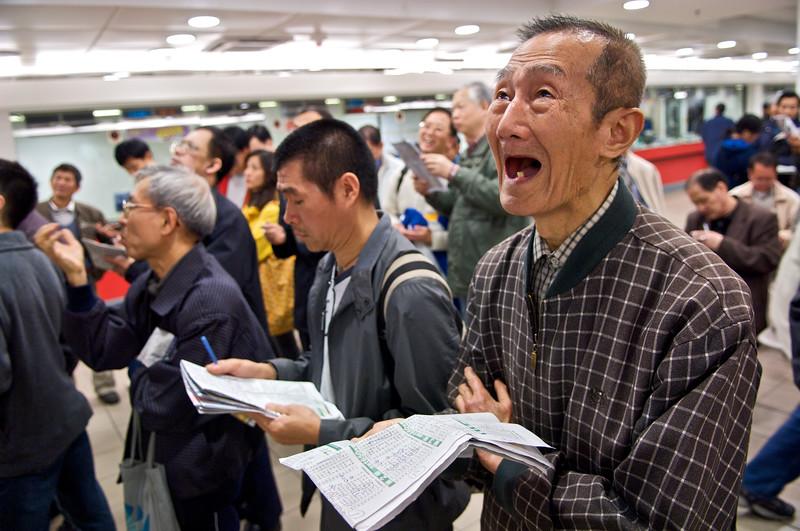 Déception d'un joueur découvrant le résultat d'une course sur l'écran d'affichage d'une salle de l'hippodrome de Happy Valley. Hong Kong/Chine
