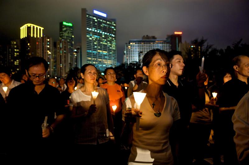 Hommes et femmes participant à la commémoration annuelle organisée à Victoria Park le soir du 4 juin en l'honneur des victimes du massacre de Tiananmen. Hong Kong/Chine