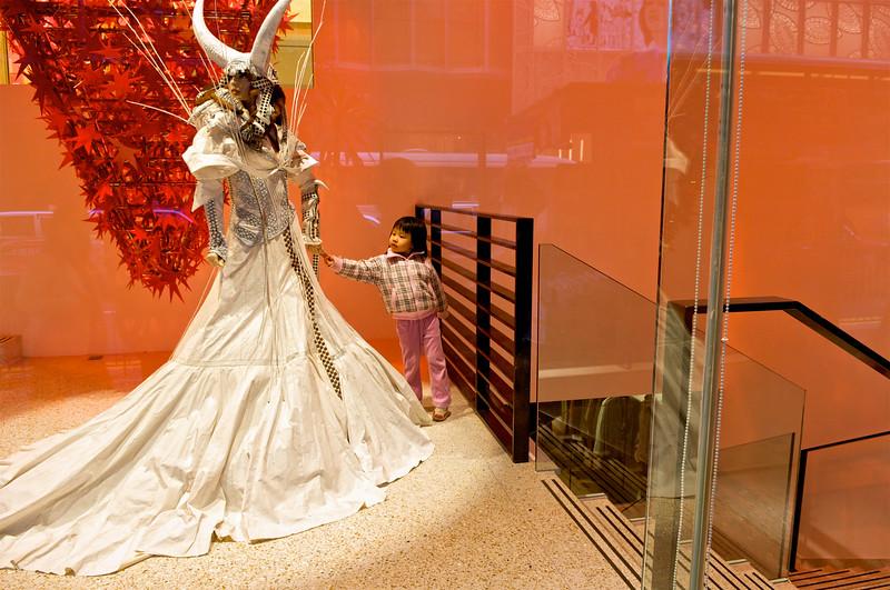 Une fillette rêvant devant le vêtement d'un mannequin installé à l'entrée d'une boutique de prêt-à-porter de luxe dans le quartier de Central. Hong Kong/Chine