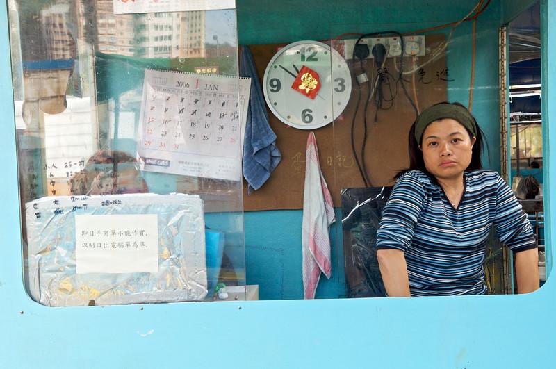 Portrait d'une femme contrôlant la pesée des marchandises dans une cabine installée au coeur du marché aux poissons d'Aberdeen. Hong Kong/Chine