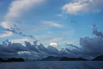 Hong Kong and Kowloon in the distance, Taken from the DB-Mui Wo Ferry. Rare for HK to get a big sky like this in the summer. Dark foreground clouds are due to the sun having passed behind the Lantau mountains behind me causing a blue shadow across the islands to the front.