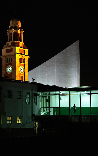 Someone watching ferries leave Star Ferry Pier.  In the background is the KCR Clock Tower and Hong Kong Cultural Center.