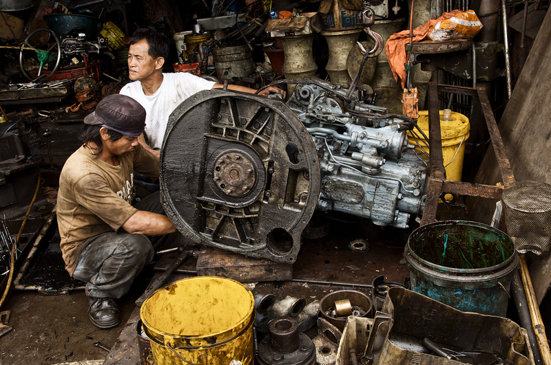 Ouvriers travaillant sur un moteur de bateau dans le petit chantier naval de l'ile de Cheung Chau. Hong Kong/Chine