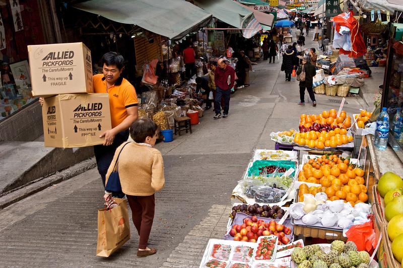 Un livreur et une cliente lilliputienne se croisant dans un marché du quartier de Soho. Hong Kong/Chine
