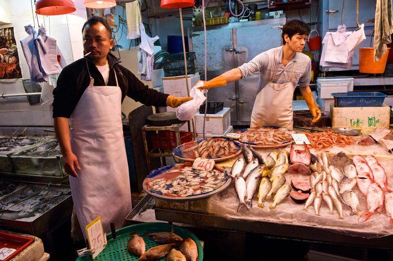 Vendeurs d'une échoppe de poissons dans le quartier de Mid-Levels. Hong Kong/Chine